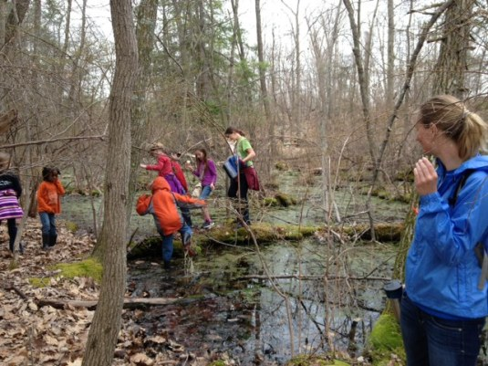 Kids from the Hudson Valley Homeschool Roots & Shoots group explore a vernal pool with Scenic Hudson environmental educator, Abi.