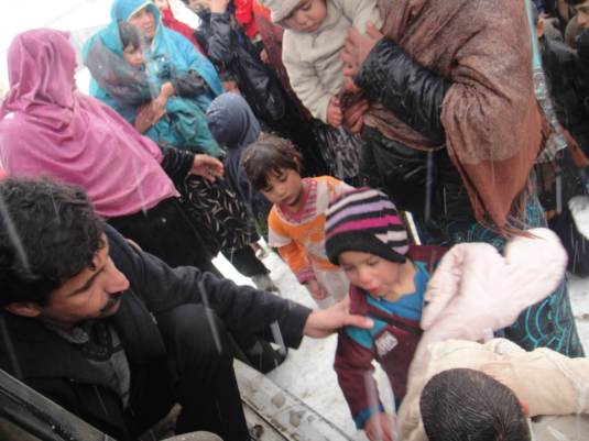 Aschiana's photo of their aid workers handing out clothing to displaced children in the camps